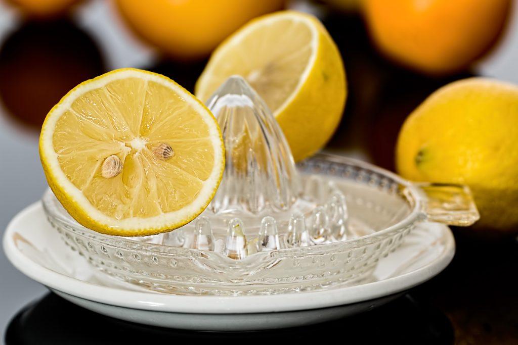 presse agrumes en verre et citrons jaunes