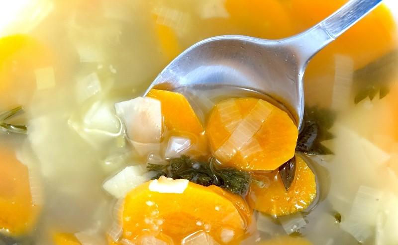 une cuillère à soupe plongée dans de la soupe de légumes