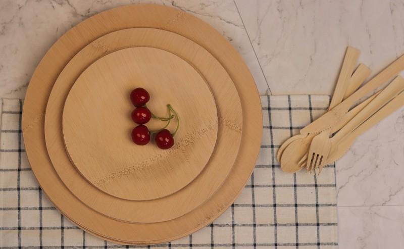 assiette en bambou et des couverts en bambou posés sur un torchon à carreaux