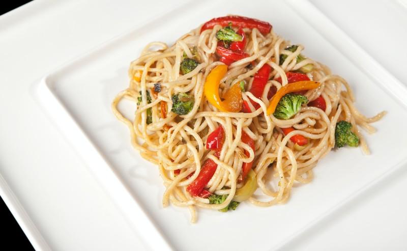 assiette carrée avec des spaghettis aux legumes posée sur la table