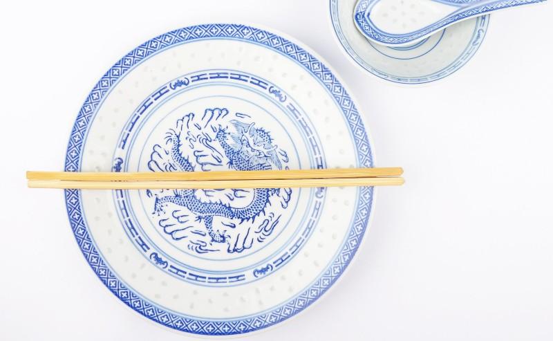 assiette chinoise avec des baguettes posée sur la table