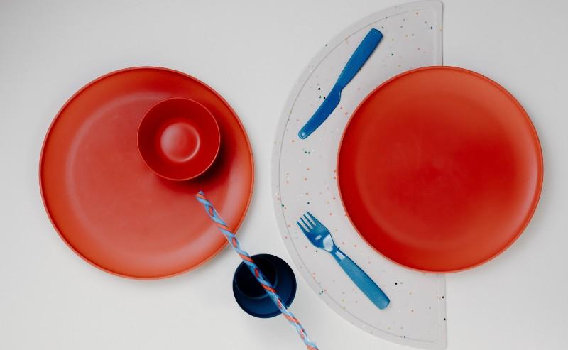 table mise pour deux. Sur cette table on y voit deux assiettes rouge et des couverts bleus