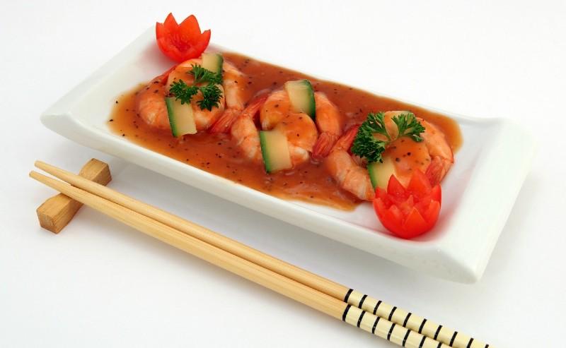 baguette chinoise positionnées proche d'une assiette avec des crevettes en sauce