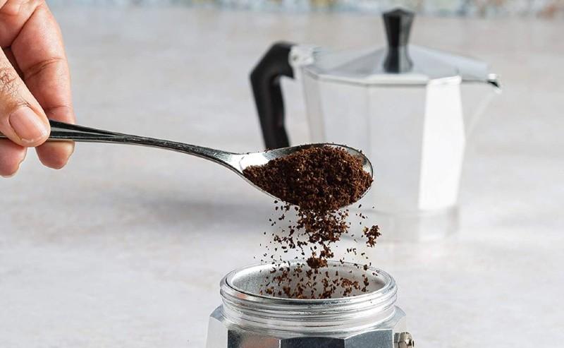 un homme versant du café dans le compartiment de la cafetière italienne