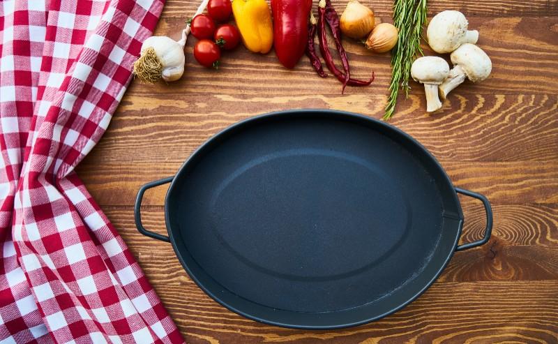 une casserole posé sur un plan de travail en bois et autour des petits légumes