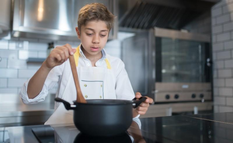 un enfant devant une plaque de cuisine en remuant àl'aide d'une cuillère dans une casserole induction