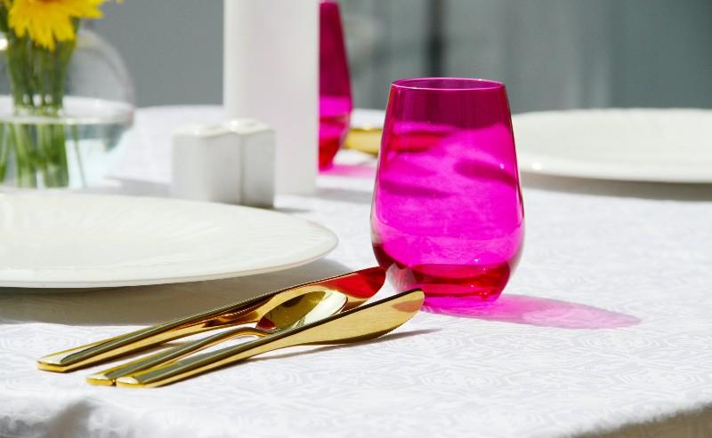 couvert doré positionnés proche d 'une assiette blanche et d'un verre rose