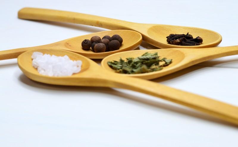 cuillère en bois avec différentes épices dedans posées sur un plan de travail