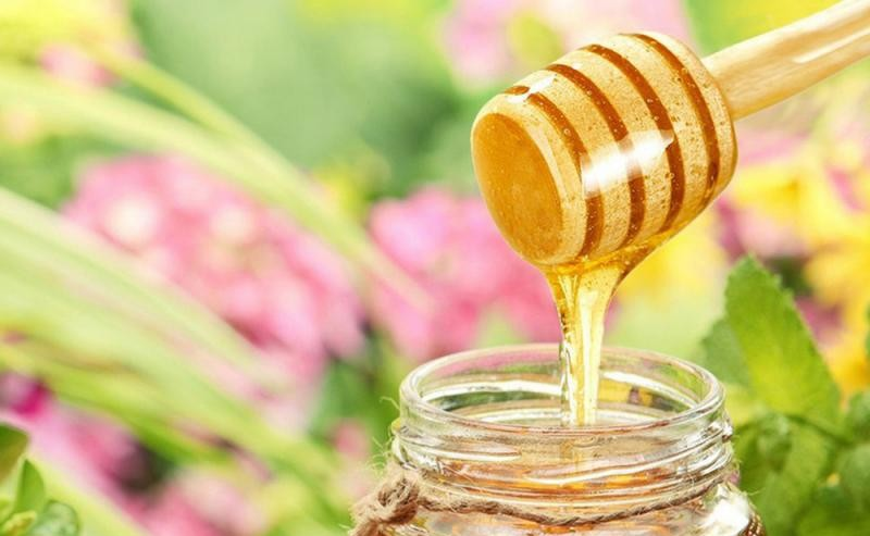 une cuillère à miel au dessus d'un pot de miel