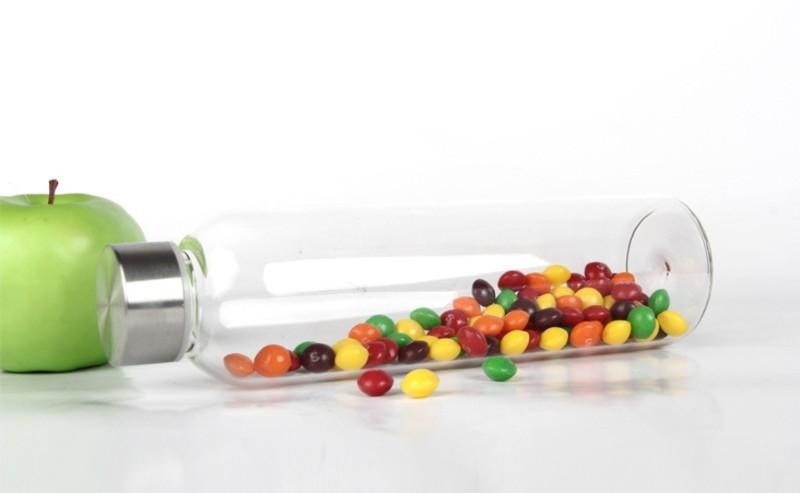 gourde en verre avec des petite bonbons multicolores sur un plan de travail