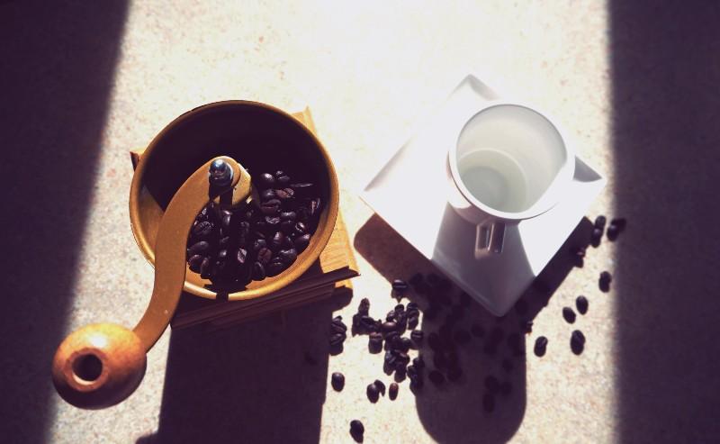 une tasse à café blanche à coté d'un moulin à café