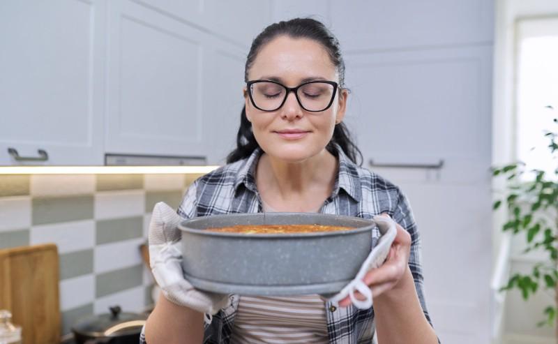 jeune femme tenant un gâteau fraîchement sorti du four