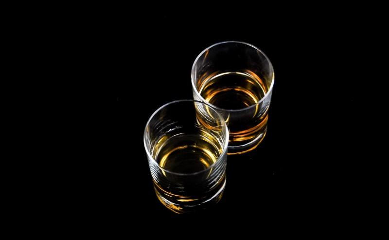 deux verres à rhum posés sur une table noire