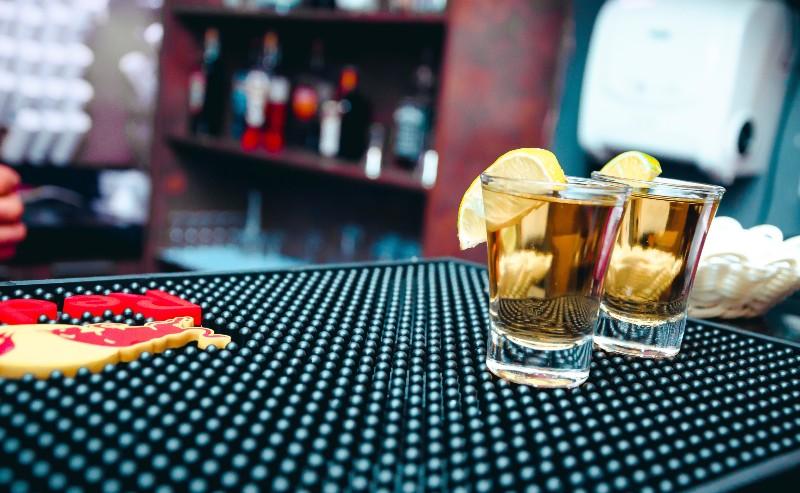 téquila dans un verre shot posé sur un comptoir de bar