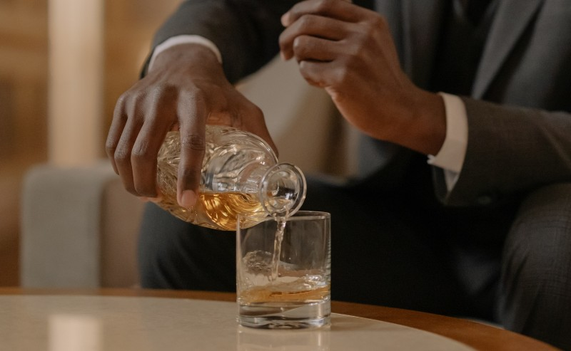 un homme se servant un verre de whisky