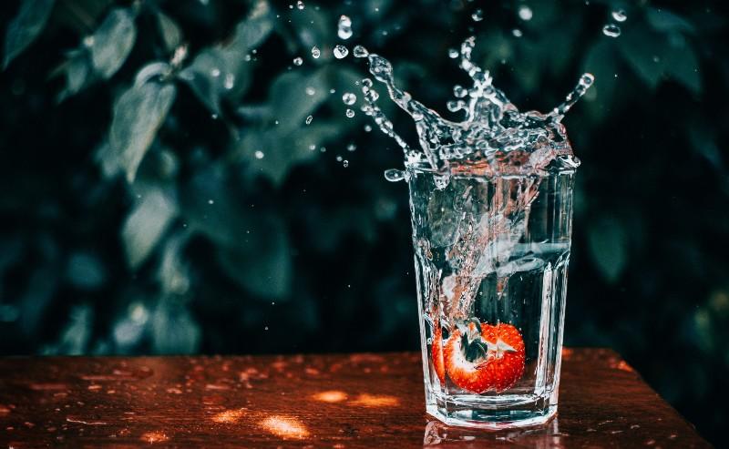 un verre d'eau avec une fraise